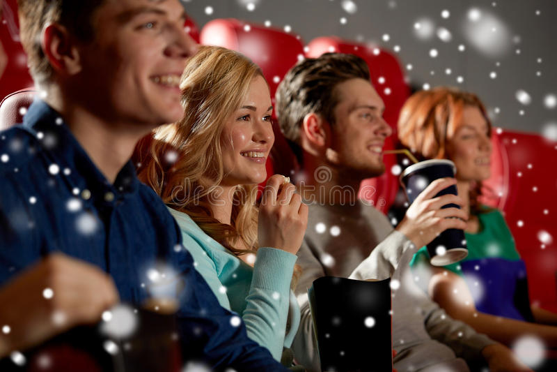 Amigos felices con palomitas y bebidas en cine imágenes de archivo libres de regalías