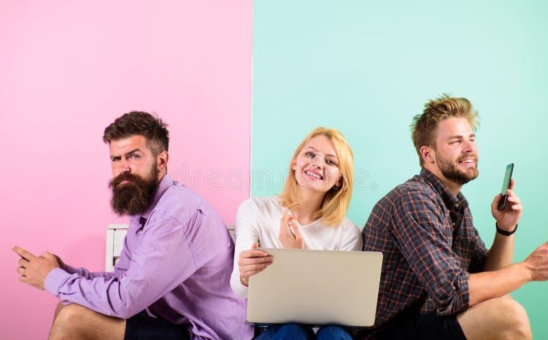 Amigos felices de la compañía con el ordenador portátil móvil de los artilugios Los hombres y la mujer tienen acceso a Internet d fotos de archivo