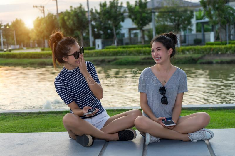Amigos felices de las mujeres que hablan y que ríen el chisme que sostiene el teléfono móvil en un aire libre del parque con el f fotos de archivo