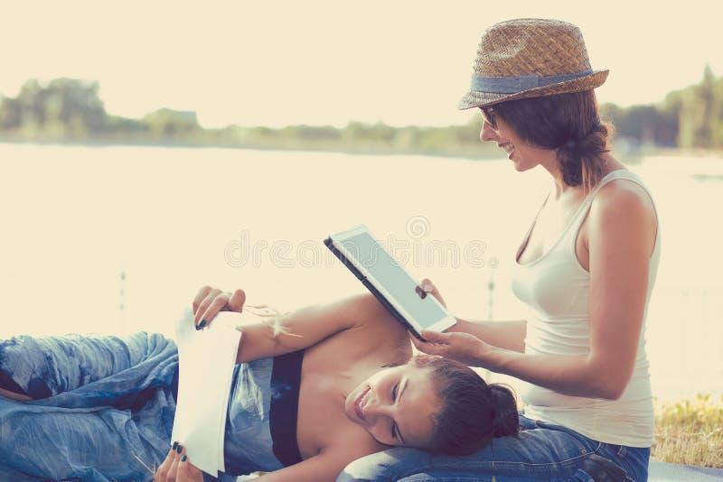 Amigos felices de las mujeres que se relajan al aire libre en prado verde en día de primavera soleado imagen de archivo libre de regalías