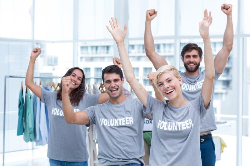 Amigos felices de los voluntarios que aumentan los brazos imagenes de archivo
