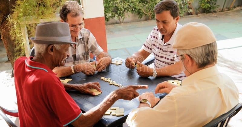 Amigos felices del retiro activo viejos que juegan al juego del dominó imagenes de archivo