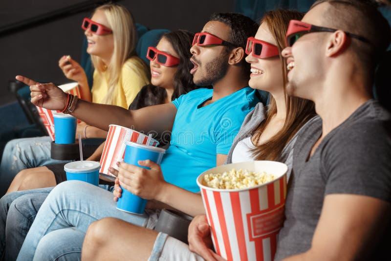 Amigos felices en el cine foto de archivo