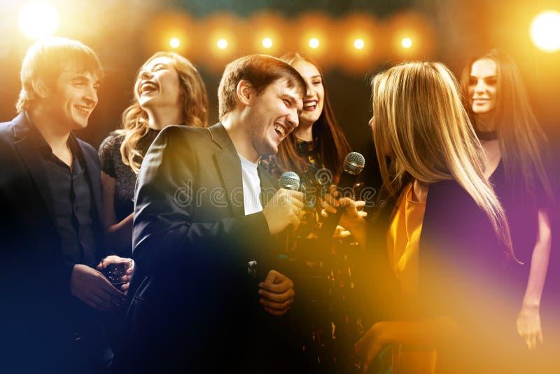 Amigos felices en el club de noche del partido del Karaoke imagen de archivo