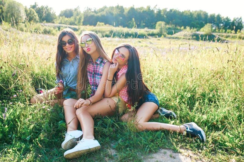 Amigos felices en el parque en un día soleado El retrato de la forma de vida del verano de tres mujeres del inconformista disfrut imagen de archivo