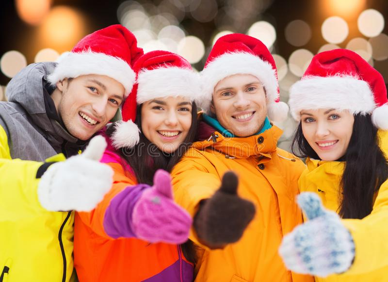 Amigos felices en los sombreros de santa y los trajes de esquí al aire libre imagenes de archivo
