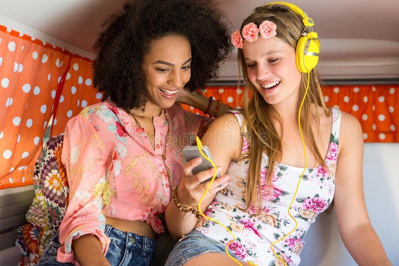 Amigos felices en un viaje por carretera usando escuchar la música imagen de archivo libre de regalías