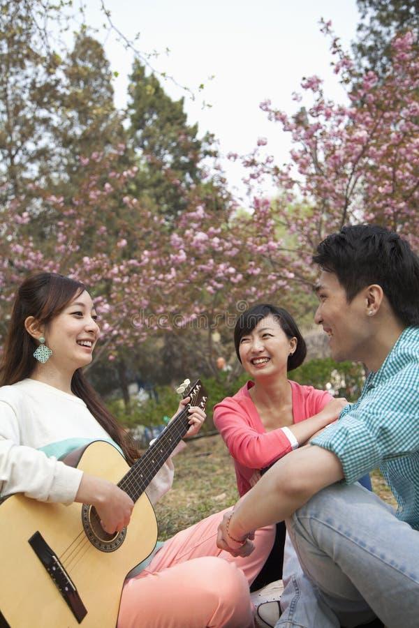 Amigos felices jovenes que cuelgan hacia fuera en el parque en la primavera, tocando la guitarra foto de archivo