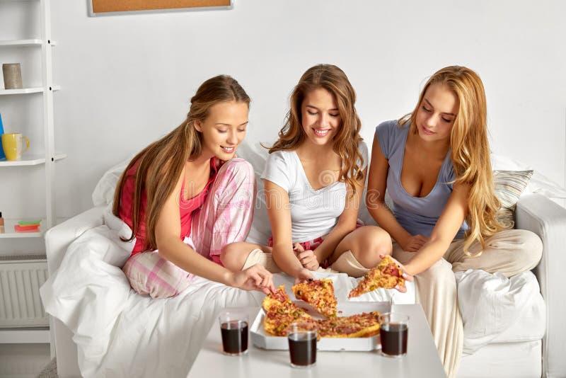 Amigos felices o muchachas adolescentes que comen la pizza en casa imagenes de archivo