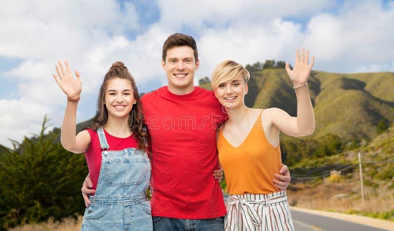 Amigos felices que abrazan sobre las colinas y el camino de Big Sur foto de archivo libre de regalías