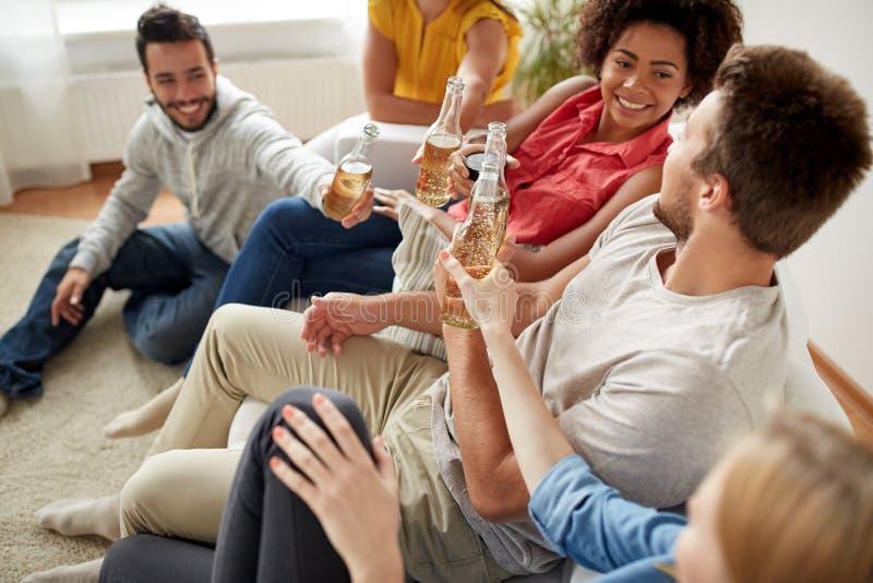 Amigos felices que beben el partido de la cerveza en casa imágenes de archivo libres de regalías