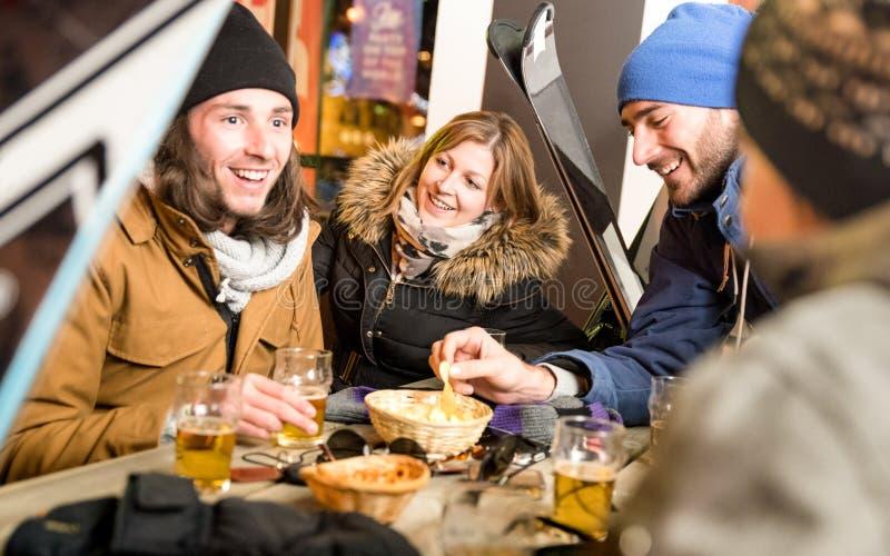 Amigos felices que beben la cerveza y que comen microprocesadores en el chalet de la estación de esquí imagenes de archivo