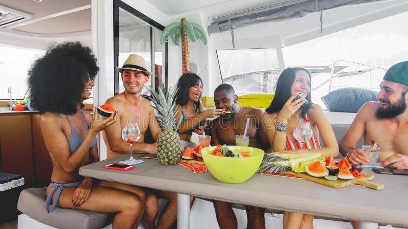 Amigos felices que beben y que comen las frutas en el partido en el barco fotografía de archivo libre de regalías