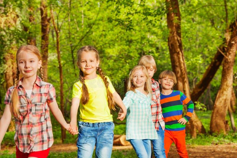 Amigos felices que caminan en el bosque que lleva a cabo las manos foto de archivo libre de regalías