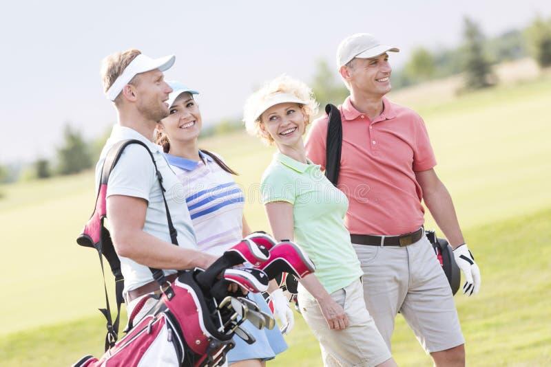 Amigos felices que caminan en el campo de golf fotos de archivo libres de regalías