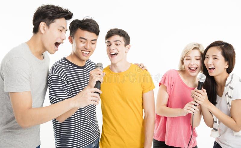 Amigos felices que cantan la canción junto imagen de archivo