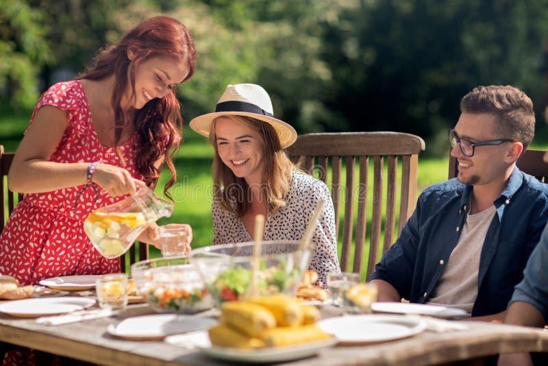 Amigos felices que cenan en la fiesta de jardín del verano foto de archivo