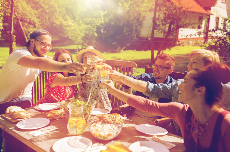 Amigos felices que cenan en la fiesta de jardín del verano fotografía de archivo libre de regalías