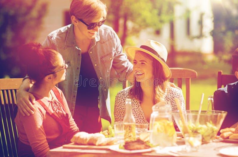 Amigos felices que cenan en la fiesta de jardín del verano imágenes de archivo libres de regalías
