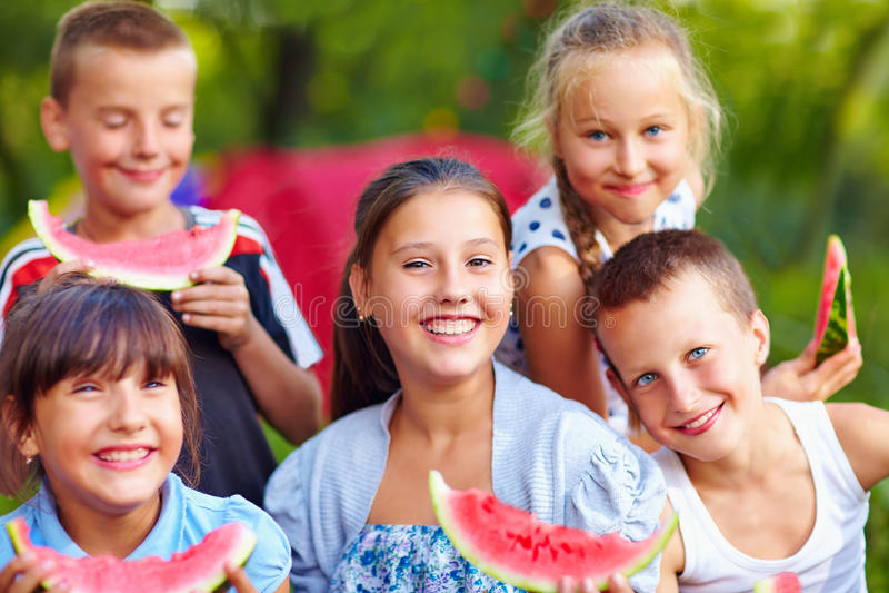 Amigos felices que comen la sandía, al aire libre fotos de archivo libres de regalías