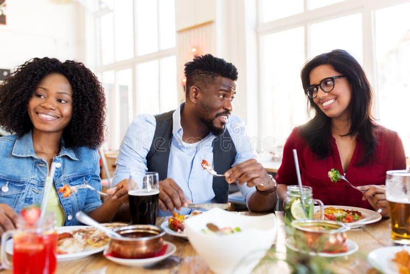 Amigos felices que comen y que hablan en el restaurante foto de archivo libre de regalías
