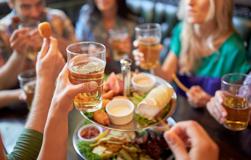 Amigos felices que comen y que beben en la barra o el pub fotos de archivo