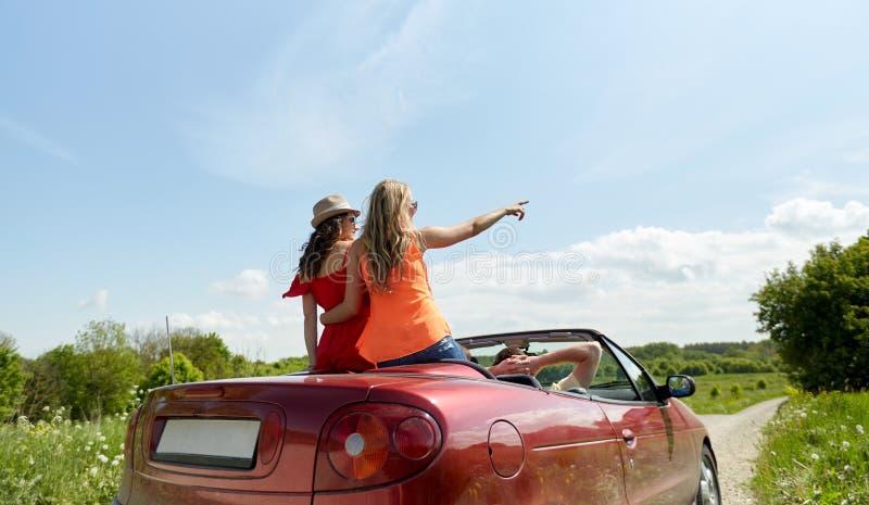 Amigos felices que conducen en coche del cabriolé en el país fotos de archivo