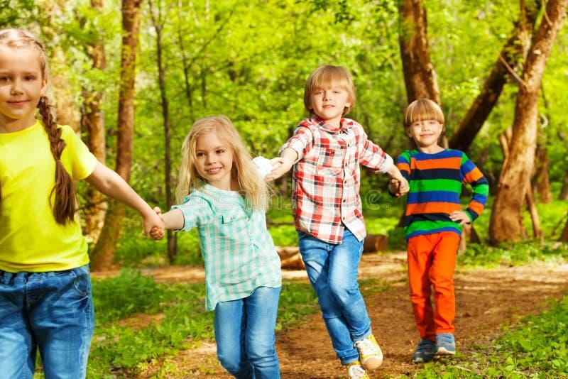 Amigos felices que corren en el bosque que lleva a cabo las manos imágenes de archivo libres de regalías