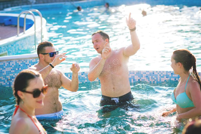 Amigos felices que disfrutan de verano en piscina fotos de archivo libres de regalías