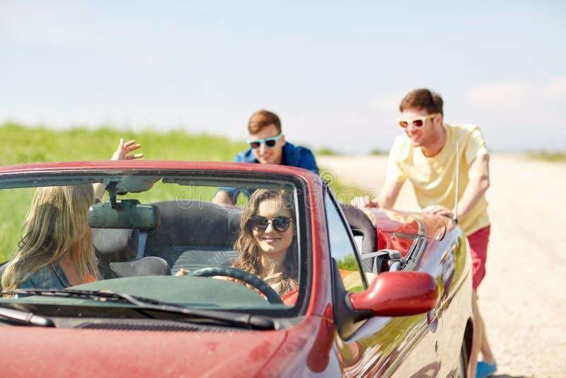 Amigos felices que empujan el coche roto del cabriolé foto de archivo libre de regalías