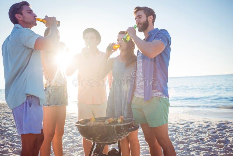 Amigos felices que hacen la barbacoa y que beben la cerveza imagen de archivo