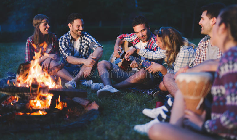 Amigos felices que juegan música y que disfrutan de la hoguera imágenes de archivo libres de regalías