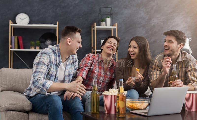 Amigos felices que miran película de la comedia foto de archivo