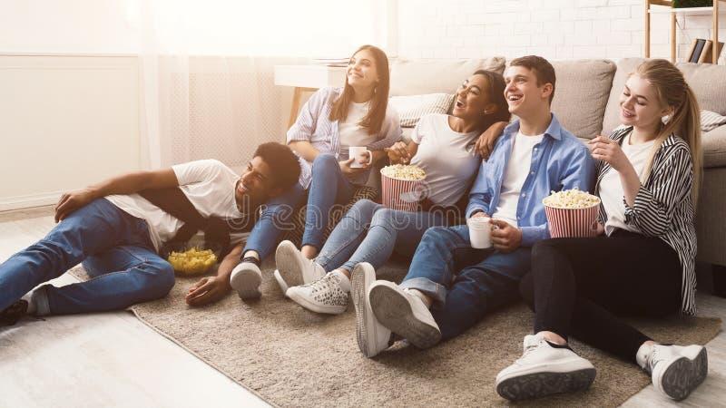 Amigos felices que miran película de la comedia en casa foto de archivo libre de regalías