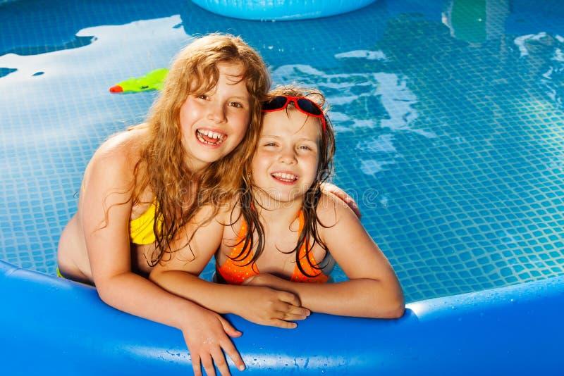 Amigos felices que presentan en la piscina inflable azul fotografía de archivo