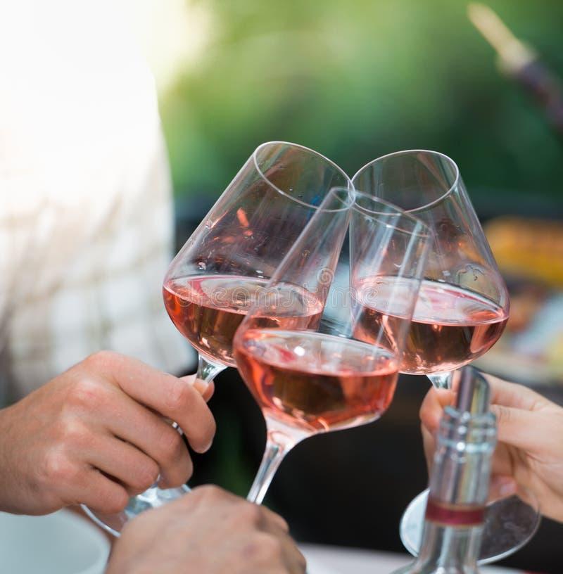 Amigos felices que se divierten al aire libre, manos que tuestan la copa de vino color de rosa foto de archivo