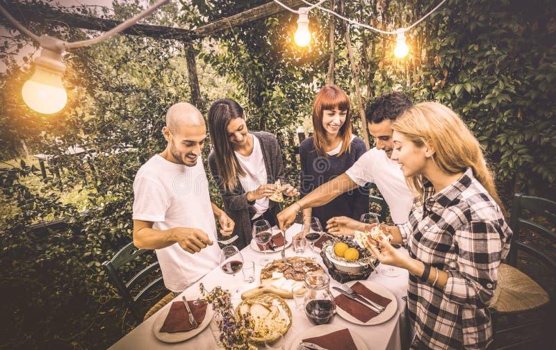 Amigos felices que se divierten que come la comida local en el partido de la comida campestre del jardín fotografía de archivo