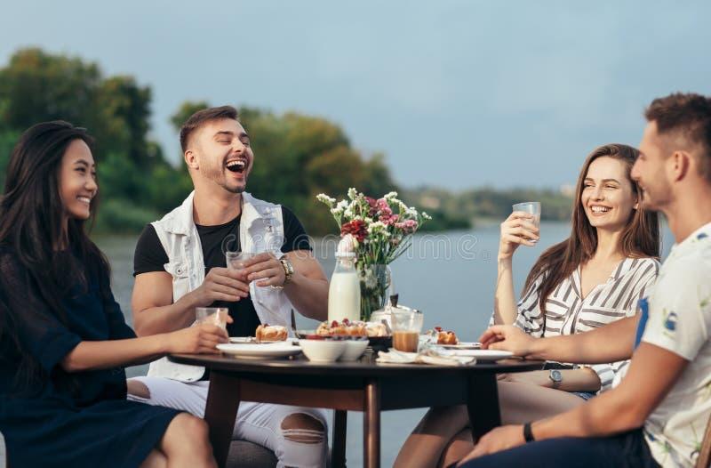 Amigos felices que se divierten durante la cena en restaurante al aire libre foto de archivo