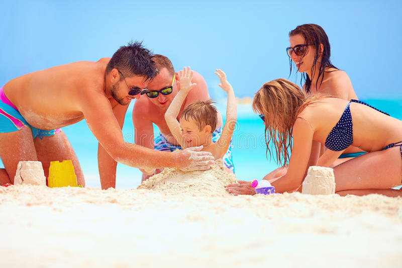 Amigos felices que se divierten en arena en la playa, vacaciones de verano imagen de archivo libre de regalías