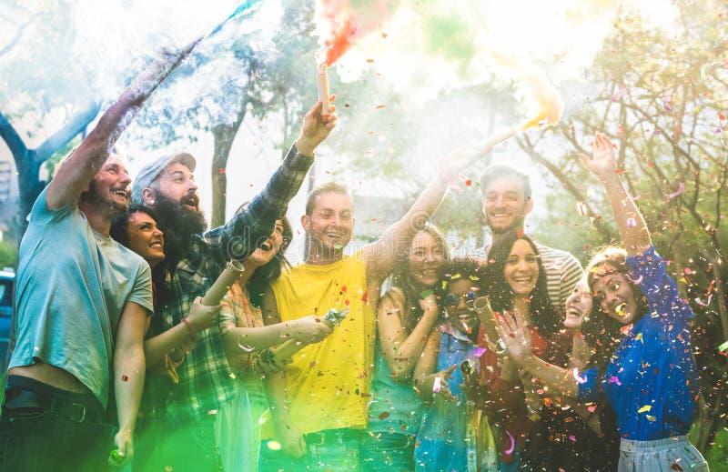 Amigos felices que se divierten en la fiesta de jardín con humo multicolor imagen de archivo libre de regalías