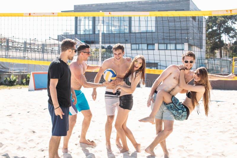 Amigos felices que se divierten en la playa en un día soleado imagenes de archivo