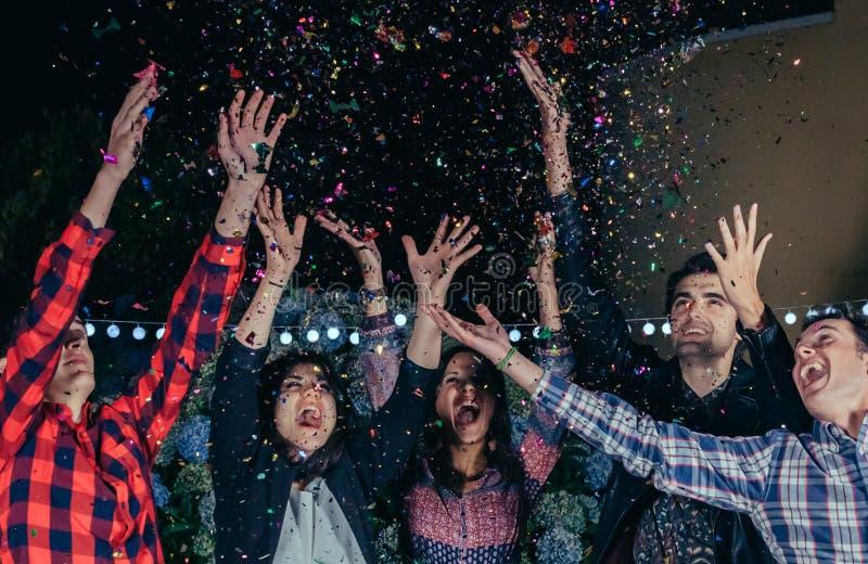 Amigos felices que se divierten entre el confeti del partido fotografía de archivo libre de regalías