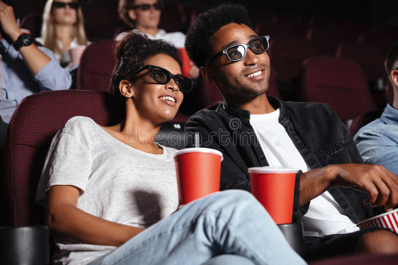 Amigos felices que se sientan en película del reloj del cine imágenes de archivo libres de regalías