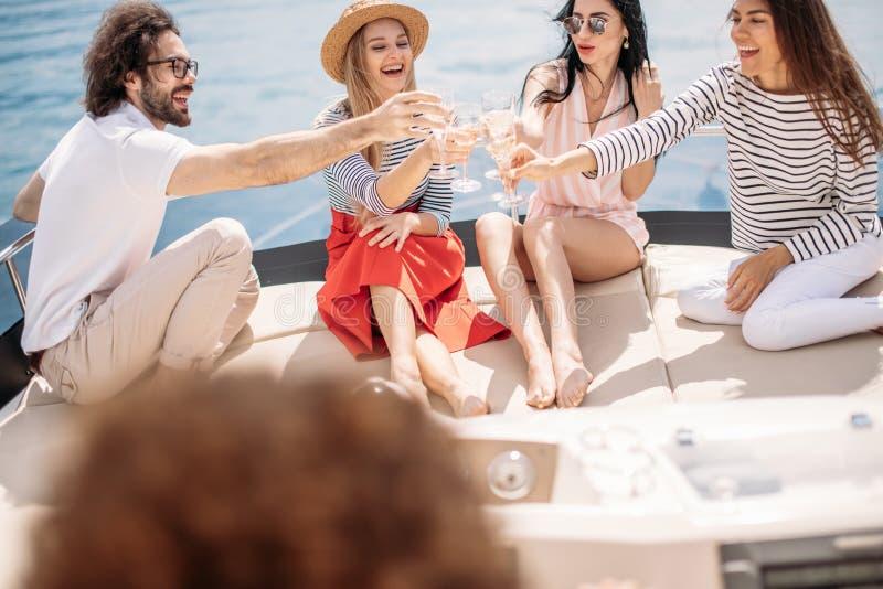 Amigos felices que tintinean los vidrios de champán y que navegan en el yate foto de archivo libre de regalías