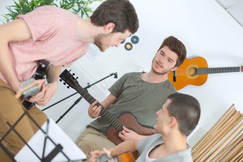 Amigos felices que tocan la guitarra y que escuchan la m?sica en casa imagen de archivo libre de regalías