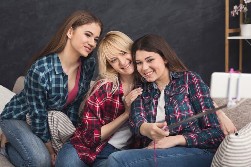 Amigos felices que toman el selfie con smartphone y el monopod fotografía de archivo libre de regalías