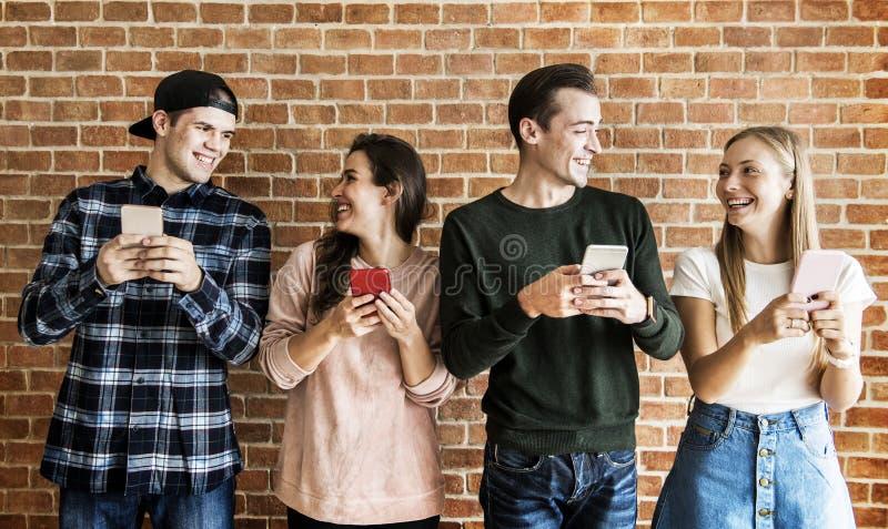 Amigos felices que usan concepto social de los smartphones medios imágenes de archivo libres de regalías