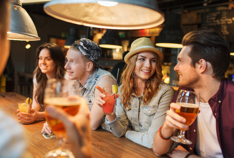Amigos felizes com bebidas que falam na barra ou no bar fotos de stock