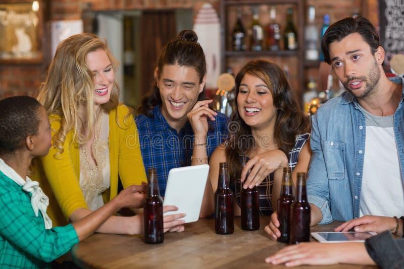 Amigos felizes com garrafas de cerveja usando a tabuleta digital imagem de stock