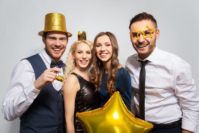 Amigos felizes com levantamento dourado dos suportes do partido fotografia de stock royalty free